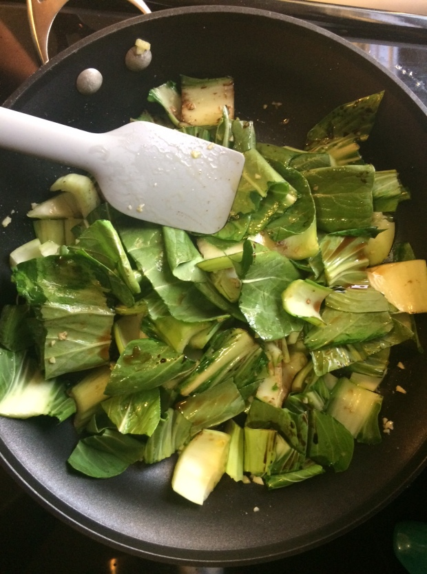 sauteeing the bok choy in ginger, oliver oil, garlic, soy sauce, and terriyaki