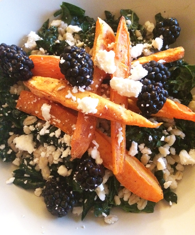 closeup of Red Quinoa and baby kale salad with sweet potato fries and blackberry dressing