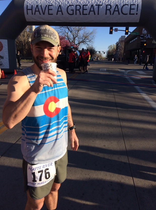 Nick drinking coffee at the start line of the Platte River Half Marathon